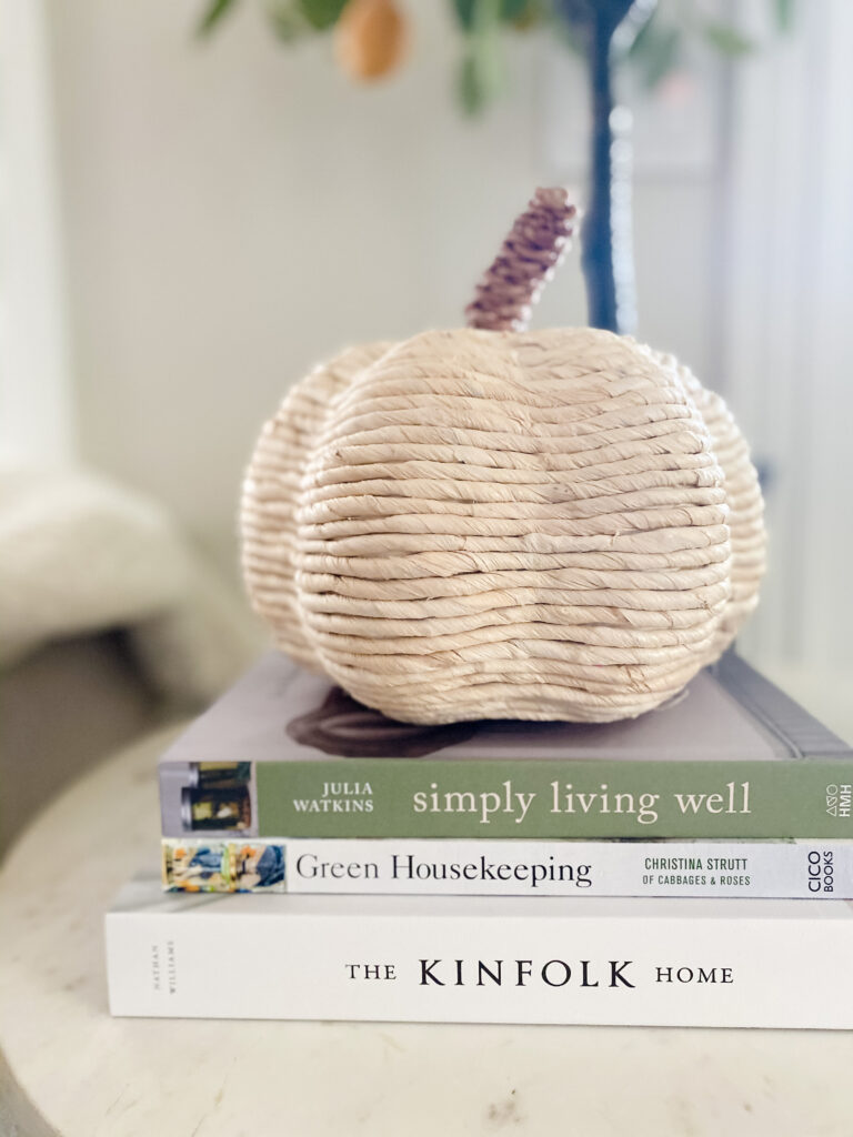Side table styped with a decorative woven pumkin and books.